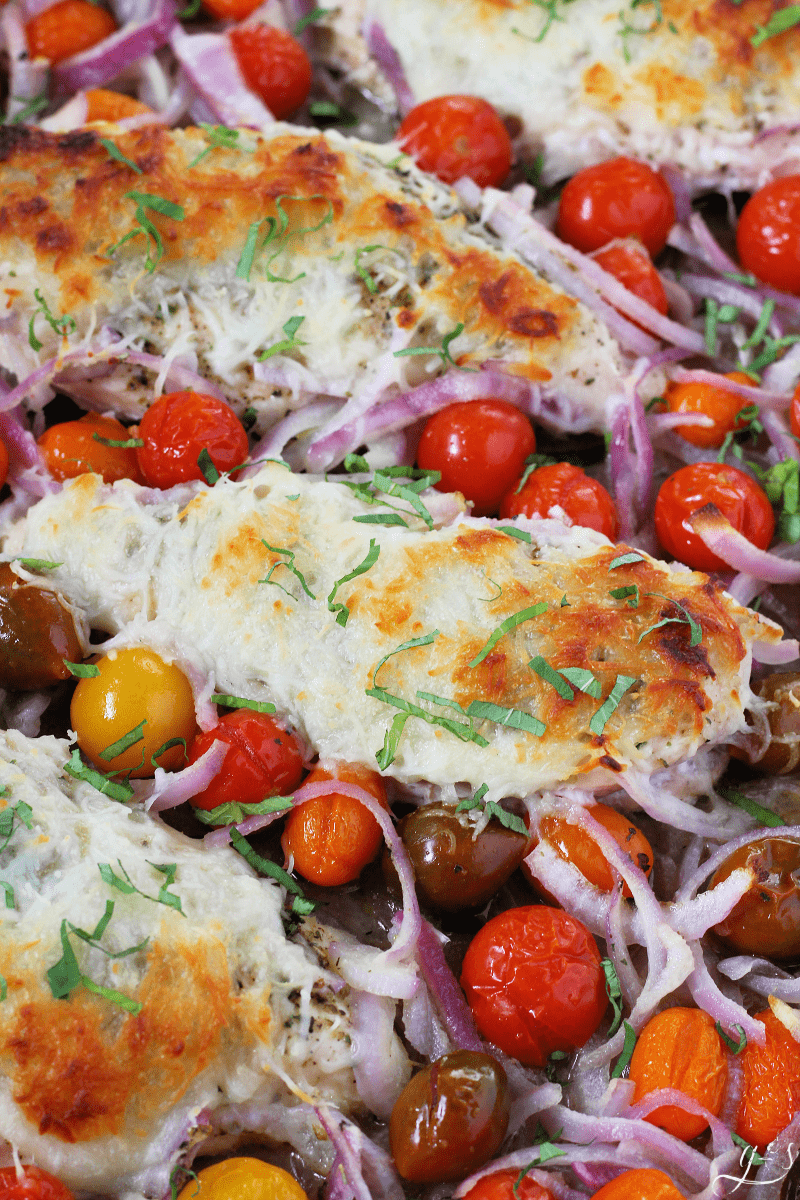 Keto Bruschetta Chicken Sheet Pan Dinner | This healthy and low carb sheet pan meal is perfect on nights when you need easy meals. Add chicken breasts, Italian seasoning, colorful cherry tomatoes, red onion, and mozzarella cheese for the best oven baked meal! You can substitute other gluten-free vegetables like broccoli, potatoes (cauliflower), or green beans too. Clean eating and meal prep have never been so delicious! Add balsamic glaze too. #glutenfree #dinner #cleaneating #easyrecipe #keto