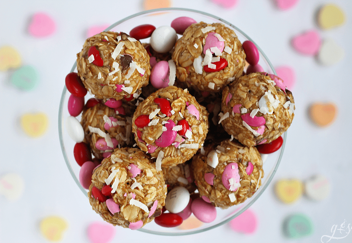 Overhead shot of Valentine Energy Bites with M&Ms in a clear glass with conversation hearts in the background.