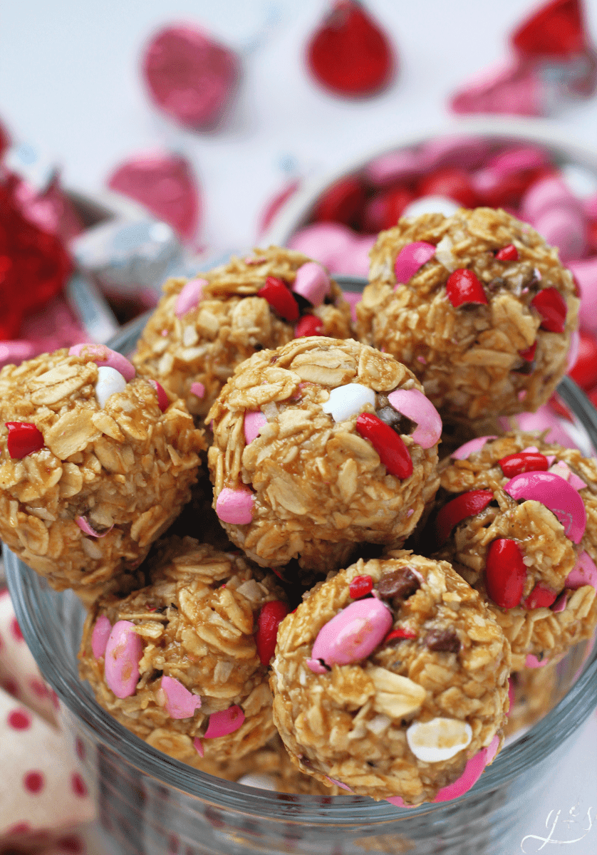 The BEST 6 Ingredient Valentine Energy Bites | This healthy no bake recipe is easy and quick to prepare. Oatmeal, flaxseed (or hemp seeds), peanut butter, M&Ms, honey, and finely shredded coconut make up these homemade gluten free goodies. Make these raw bites for kids and adults alike. Think monster cookie, but with 5 simple whole food ingredients! These Valentine treats are the perfect classroom party snack or dessert. #Valentine #snacks #glutenfree #recipes #Valentines