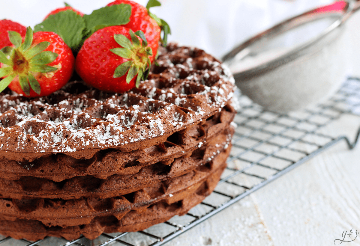 A stack of dark chocolate waffles sprinkled with powdered sugar and topped with fresh strawberries on a cooling rack.