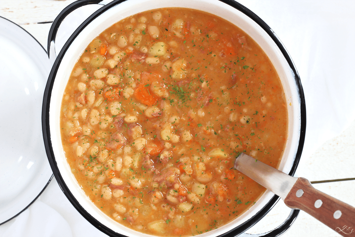 Overhead shot of bean soup in a white pot with a ladle ready to scoop it into a bowl.