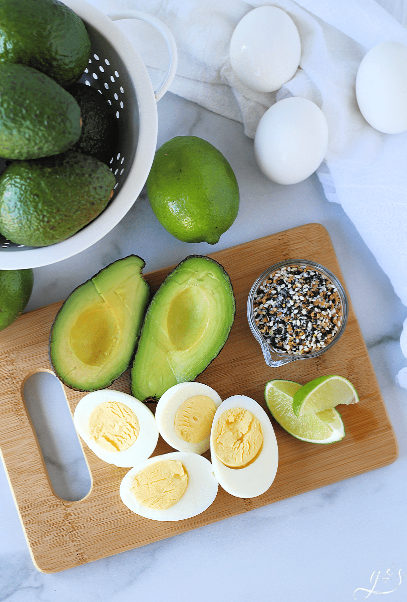 Overhead photo of avocado, hard boiled eggs, lime wedges, and EBTB seasoning on a wooden cutting board ready to be used in a 4 Ingredient Avocado Egg Salad.