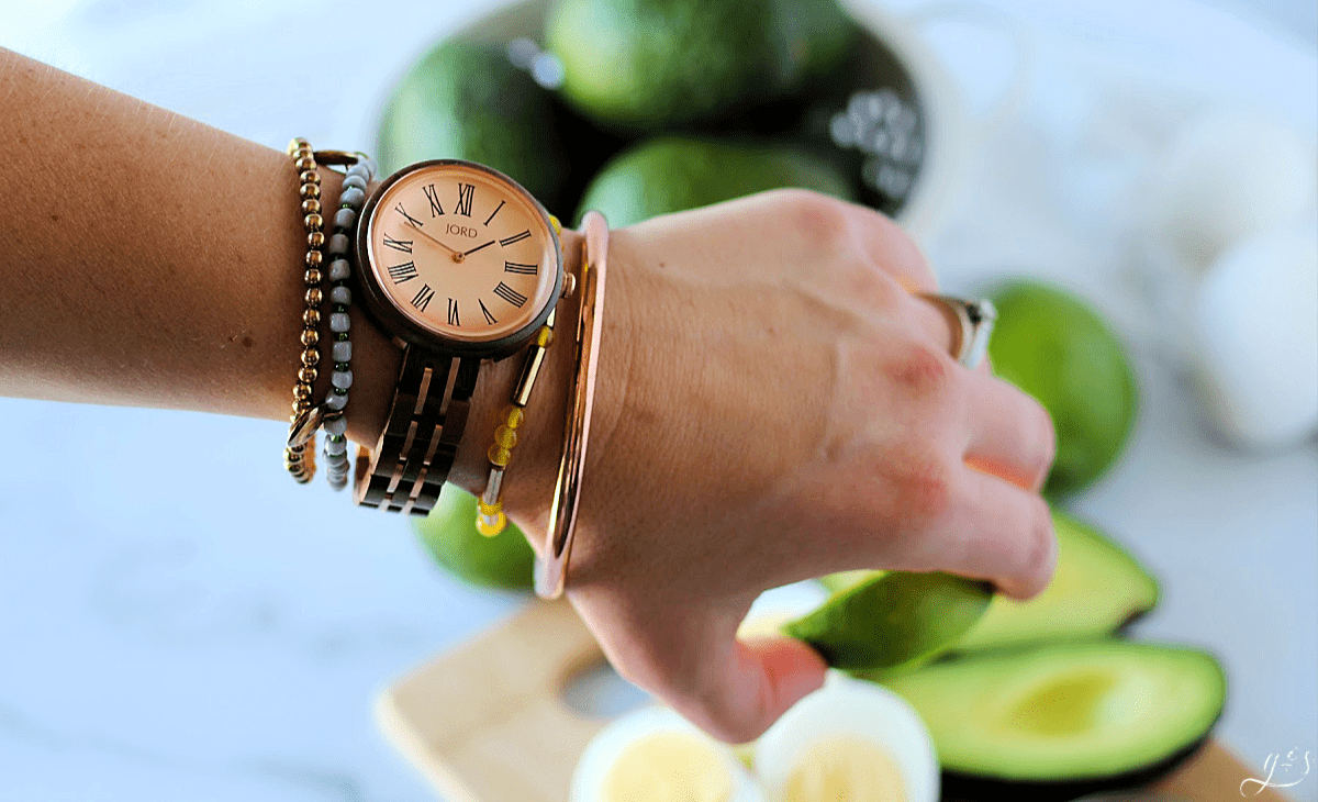 A walnut and vintage rose JORD watch on a woman's wrist with 4 bracelets.