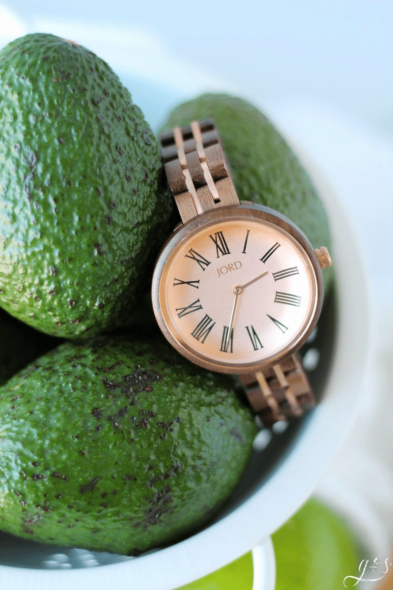 Vintage Rose and Walnut JORD watch placed on a colander of avocados.