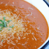 Bowl of tomato soup topped with Parmesan cheese.