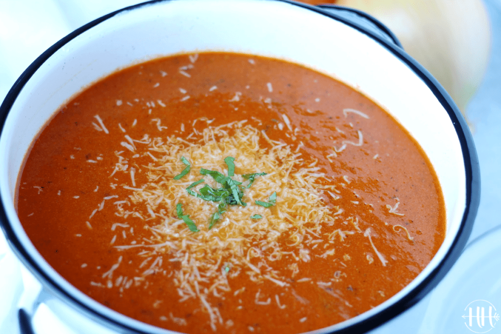 Beautiful photo of a large pot of a tomato soup recipe topped with cheese and basil.