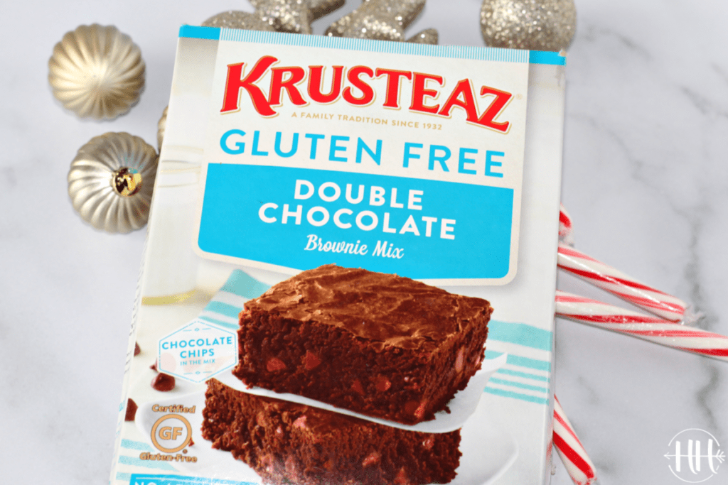 A box of Krusteaz Gluten Free Double Chocolate Brownie Mix on top of candy canes and silver Christmas tree decorations.