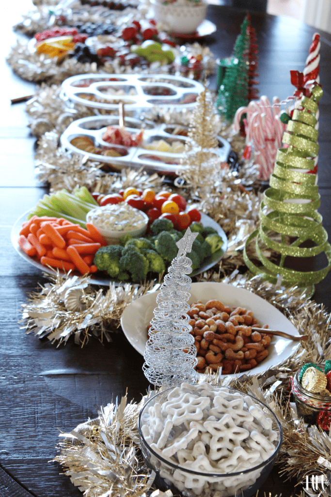 Christmas grazing table with white chocolate covered star pretzels, candied nuts, and vegetables.