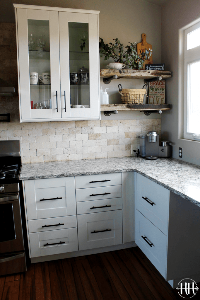 Tall wall white cabinets with rustic plant shelves and Bellingham Cambria Quartz counter top.