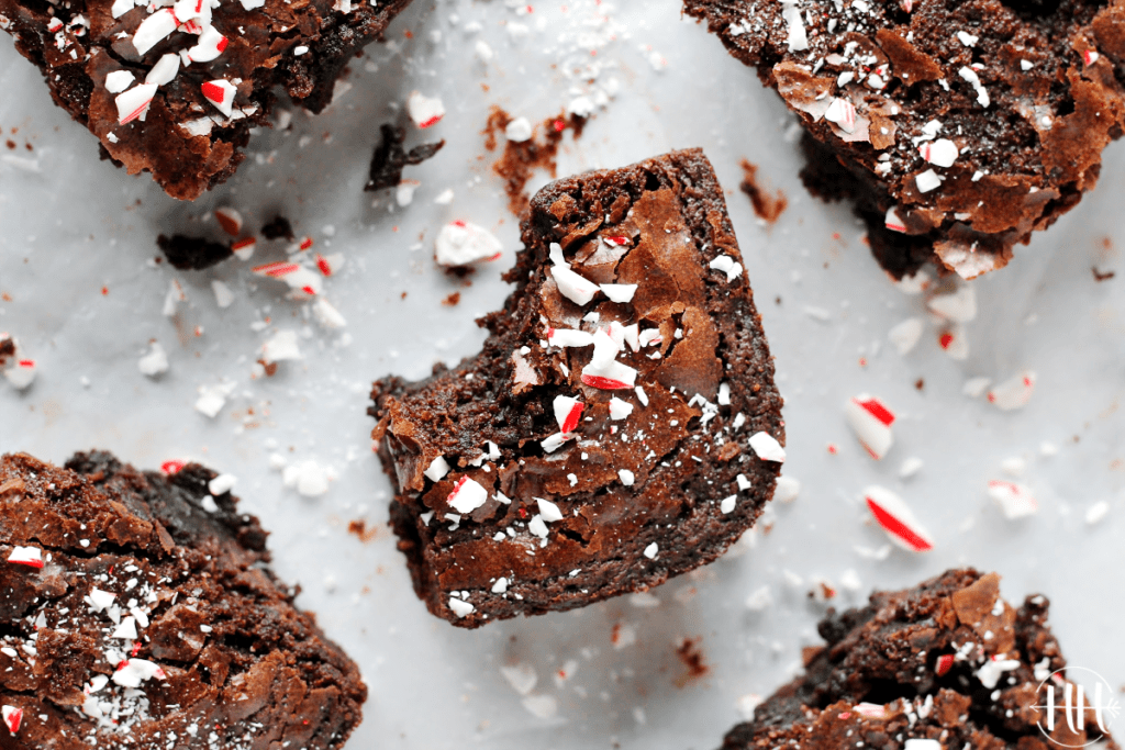 A fudgy peppermint brownie with candy cane dust sprinkled on top and a bite taken out of it.