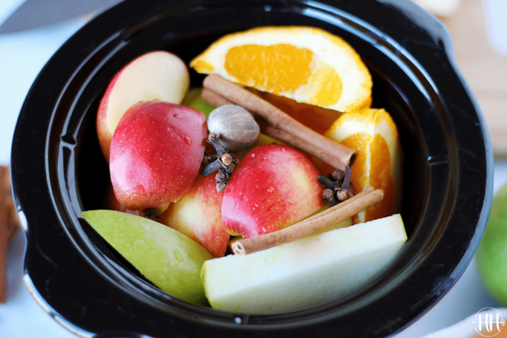 Close shot of colorful apples and orange wedges in a black small cooker insert.