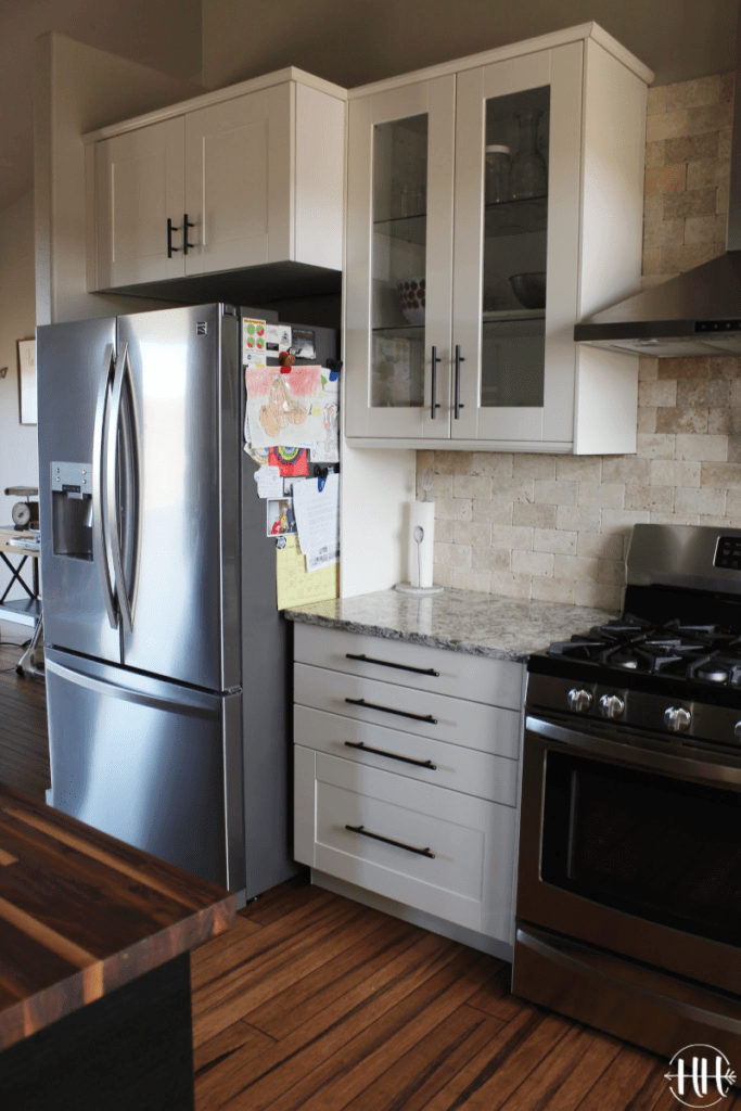 Stainless steel fridge and stove with white IKEA cabinets and Lumber Liquidators Antique Strand bamboo flooring.