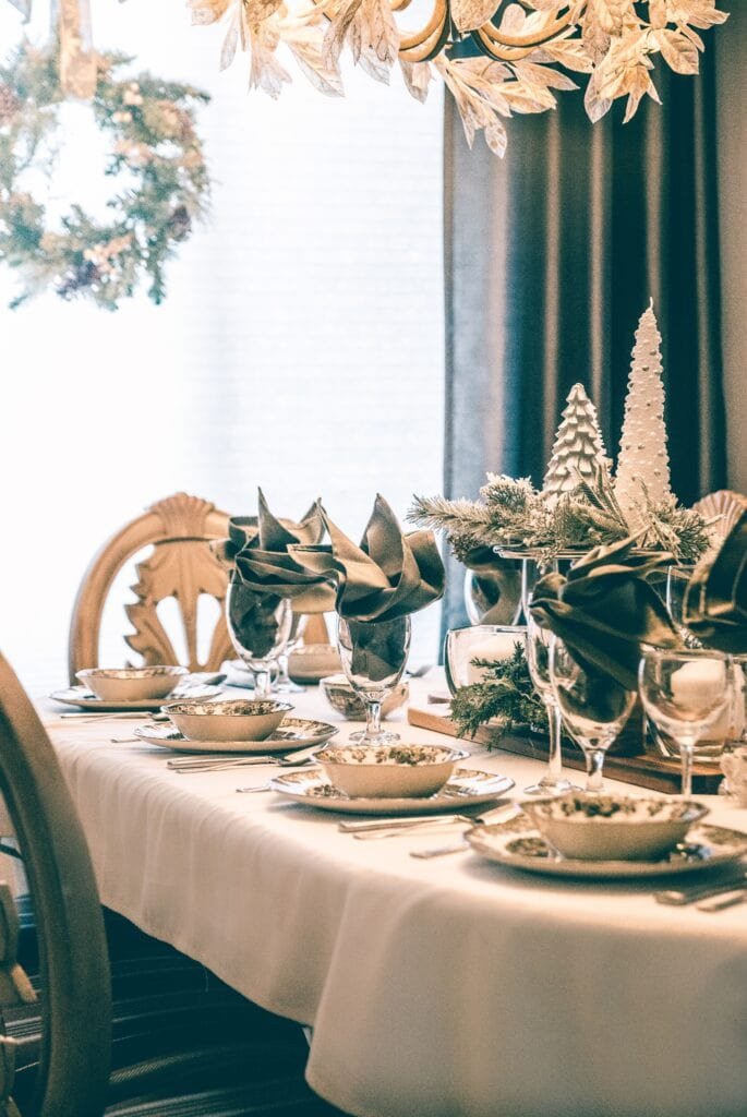 Christmas dinner table decor in whites and greens.