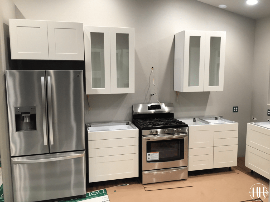 White Sektion IKEA cabinets with glass doors and stainless steel appliances.