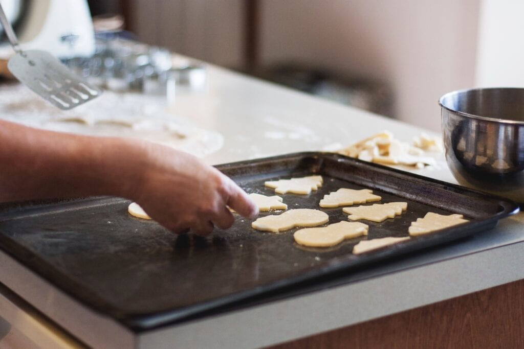 A bakers hand placing holiday sugar cookie dough on a baking sheet.