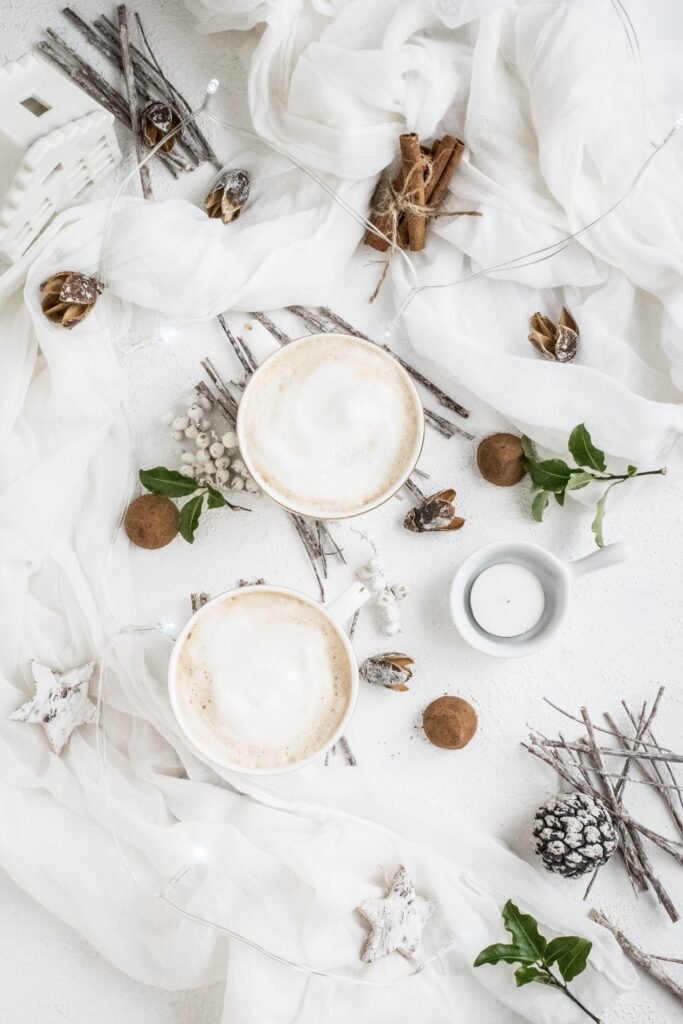 Two mugs of hot cocoa on white linens with sticks and white berries.