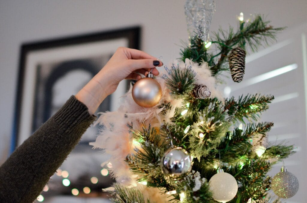 Woman's hand placing ornaments on top of Christmas tree.