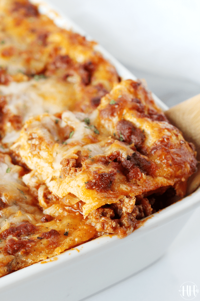 Large pan of lasagna showing the corner piece on a spatula.