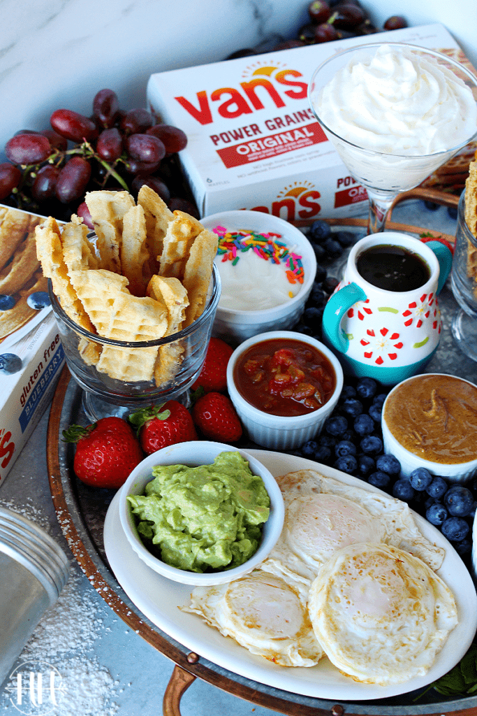 """#ad Serve this Waffle Dippers Board at your next kids party, breakfast, or brunch. Van's frozen waffles are nutritious (gluten free, whole grain-protein packed!, and organic options) and easy to make into """"soldiers"""" in this recipe idea. Use a pizza cutter to cut waffles and place on a cookie sheet, tray, or cutting board with sweet and savory dipping options like Greek yogurt, healthy nut butter, maple syrup, fruit compote, homemade whipped cream, ALL the toppings! #VansFoodsWaffles #vansfoods"""
