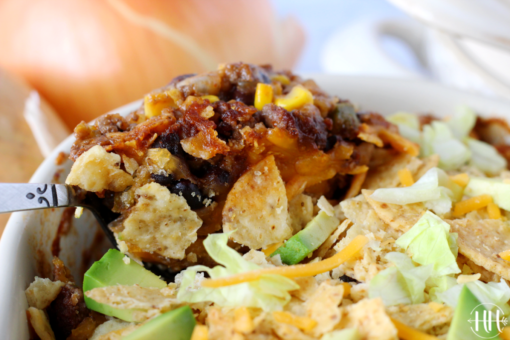 Spoonful of mexican casserole topped with crushed tortilla chips, diced avocado, lettuce, and shredded cheese.