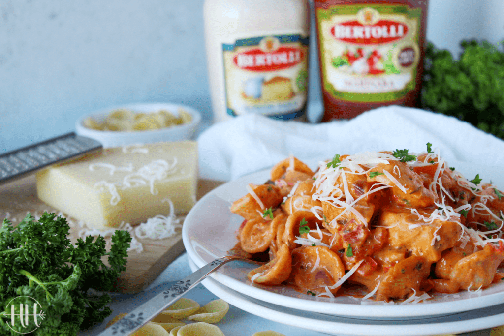 A beautiful plate of pasta in front of Bertolli Sauce jars.