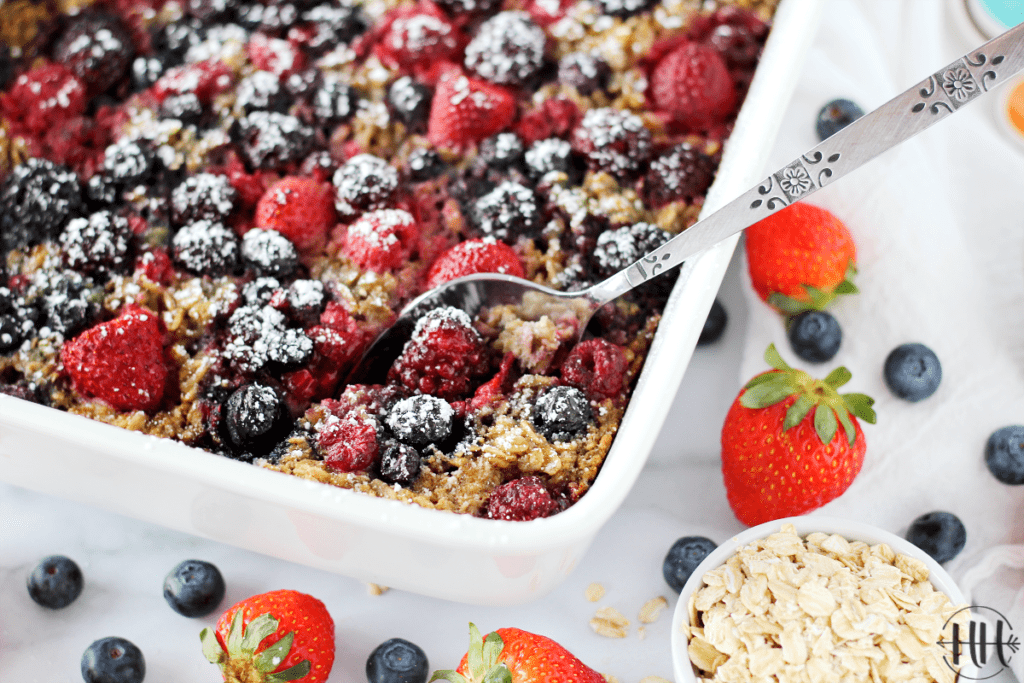 Gorgeous white dish of baked oatmeal with a spoon ready to serve.