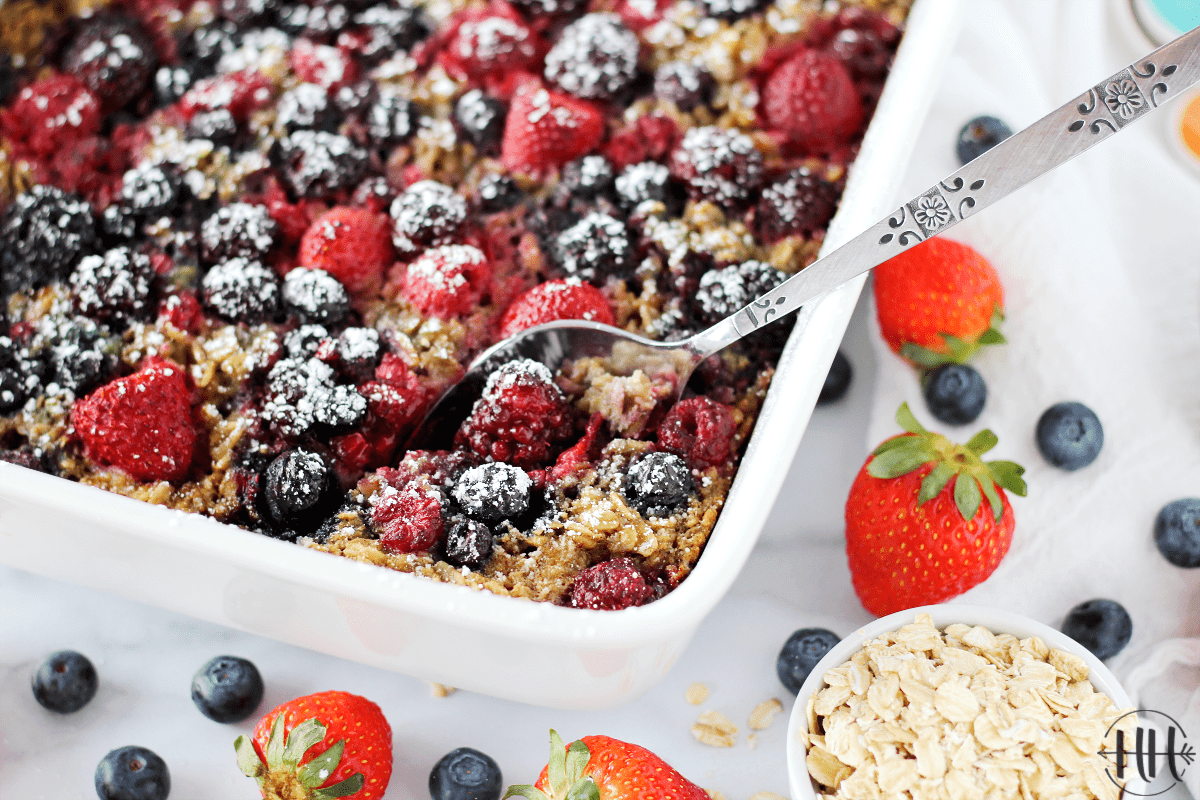 Easy Berry Baked Oatmeal - Gluten and Dairy Free recipe in a white dish surrounded by fresh berries.