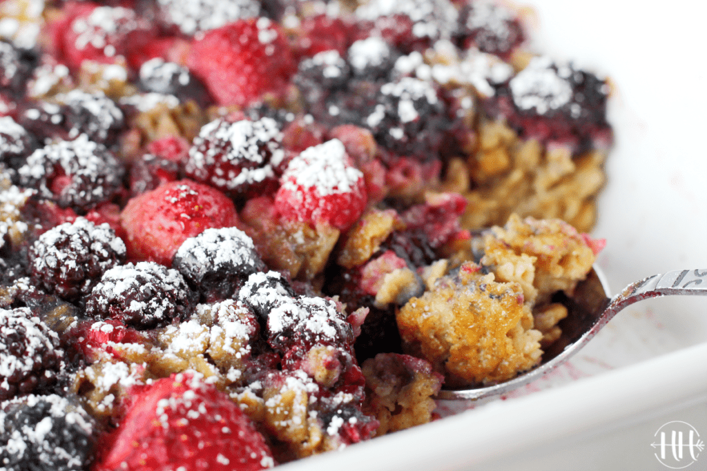 A spoon of baked oats in the pan. Pretty berries on top.