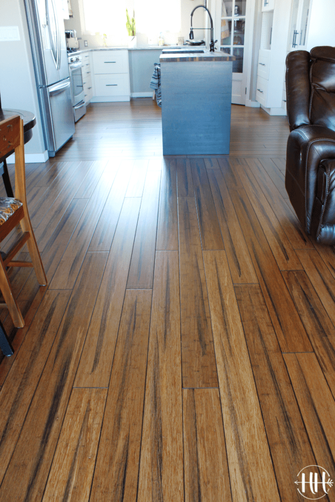 Looking from the living room to the kitchen at solid wood plank flooring.