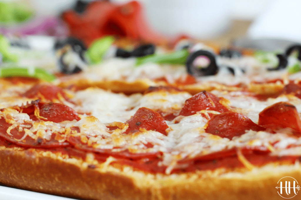 Up close shot of a pepperoni pizza with a crust of French bread.