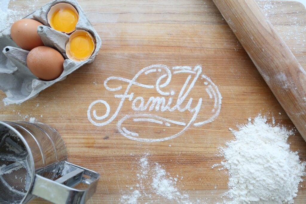A butcher block countertop with family written in flour. Possibly a play cafe.