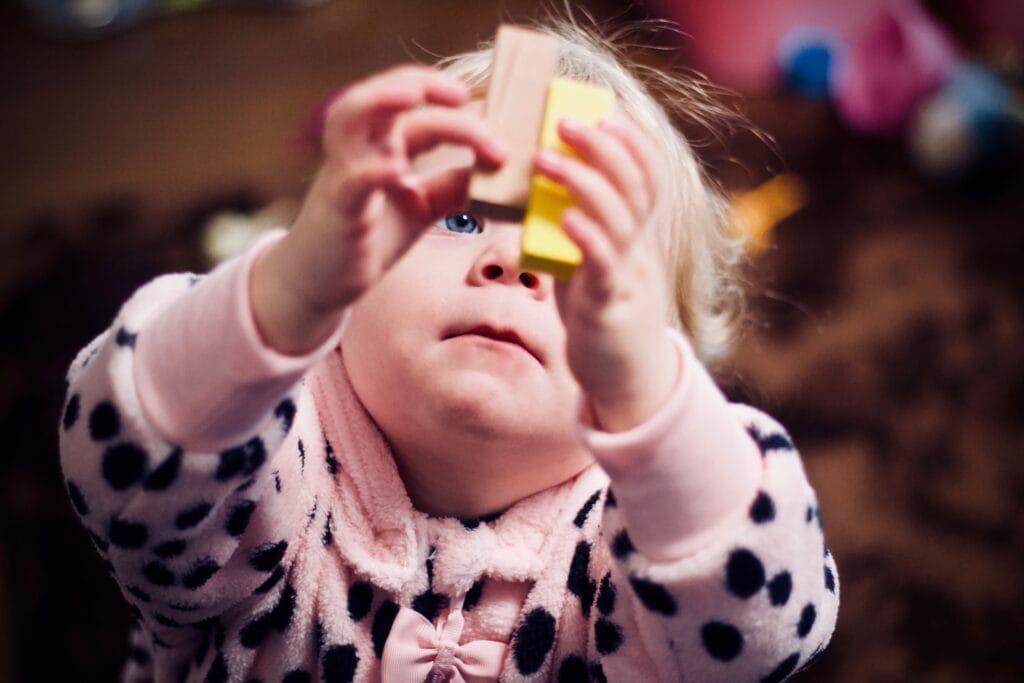 Toddler girl playing with blocks.
