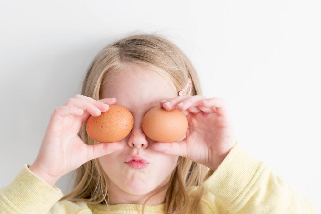 Girl holding eggs to her eyes being silly.
