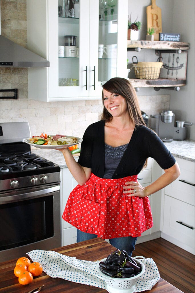 Sammi Ricke of HappiHomemade.com in her kitchen holding a charcuterie board.