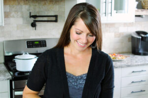 Sammi from HappiHomemade looking down and smiling in her kitchen.
