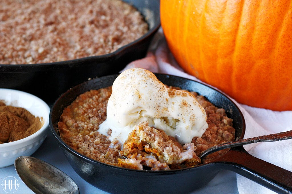 A small cast iron skillet filled with gluten free pumpkin crumble topped with vanilla ice cream.