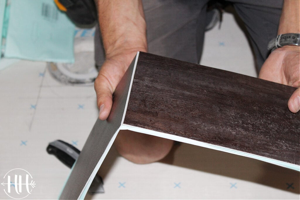 Scoring lvt with a knife then snapping it apart.