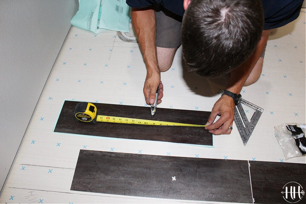 Measuring and cutting a piece of luxury vinyl tile.