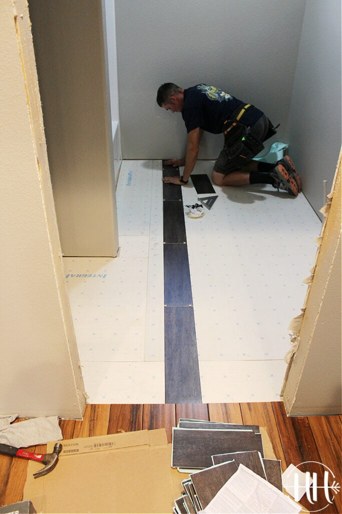 The first row of lvt being installed in a bathroom.
