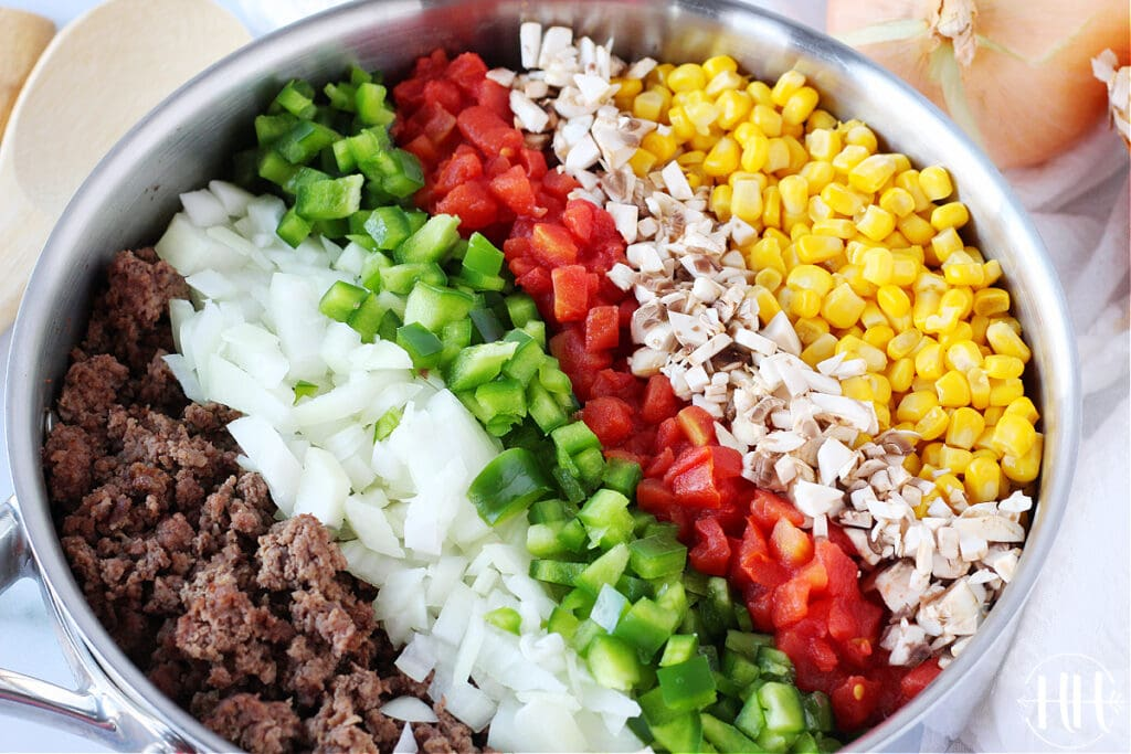 A close up photograph of ground beef, diced onion, green bell pepper, diced tomatoes, mushrooms, and canned corn in a pan.