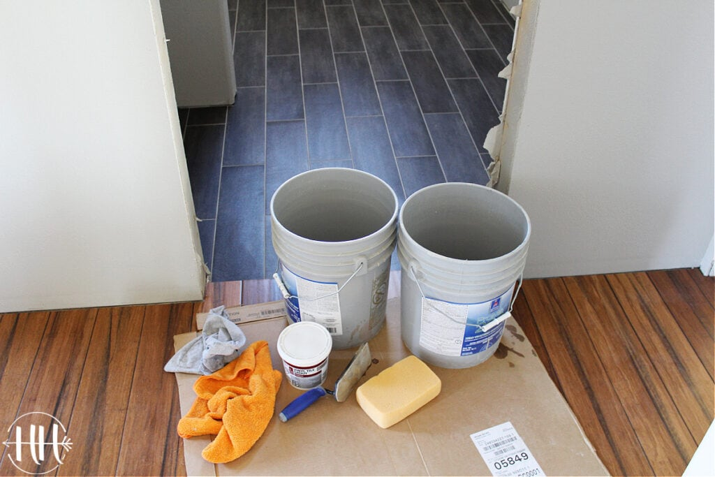 Buckets, sponge, grout float, and grout ready to be used for lvt flooring.