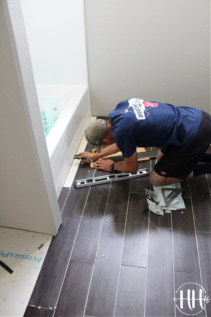 Laying the final pieces of lvt next to a bathtub.