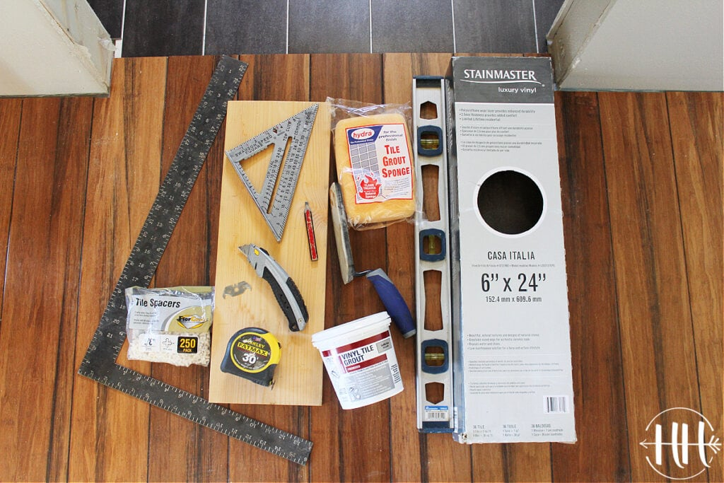 All the tools needed to install luxury vinyl planks including a level, square, and knife.
