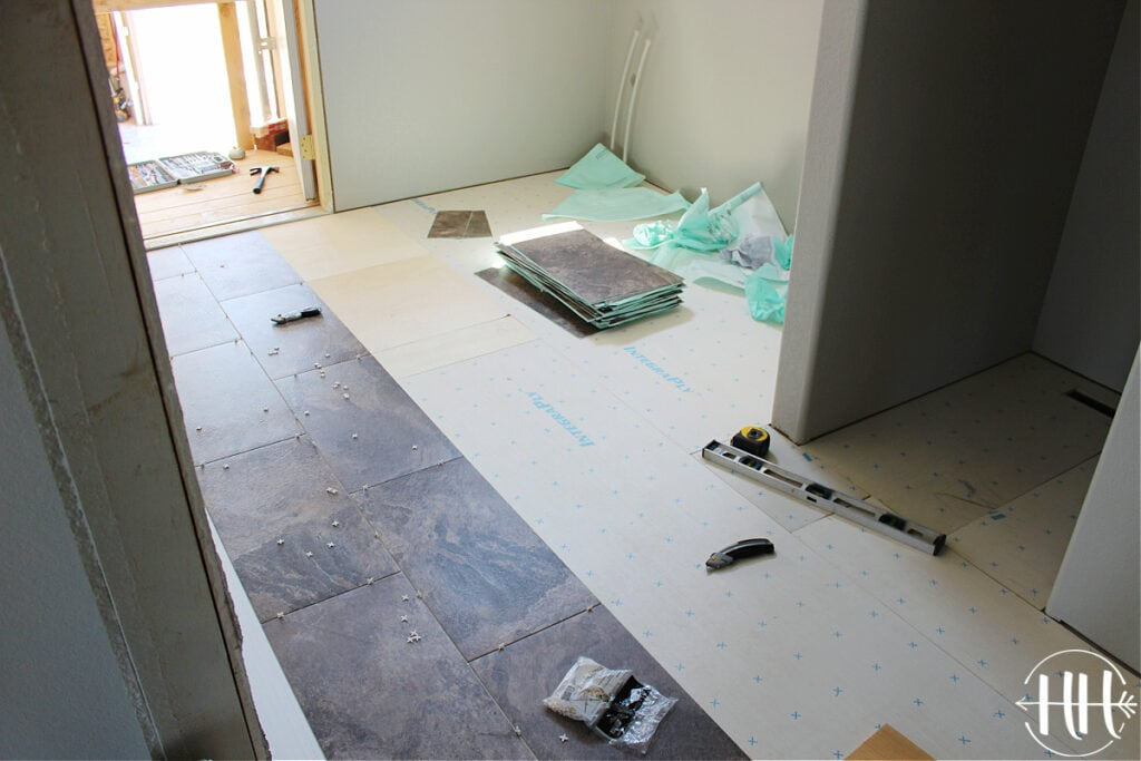 A laundry room and quarter bath with subfloor. LVT planks being laid.