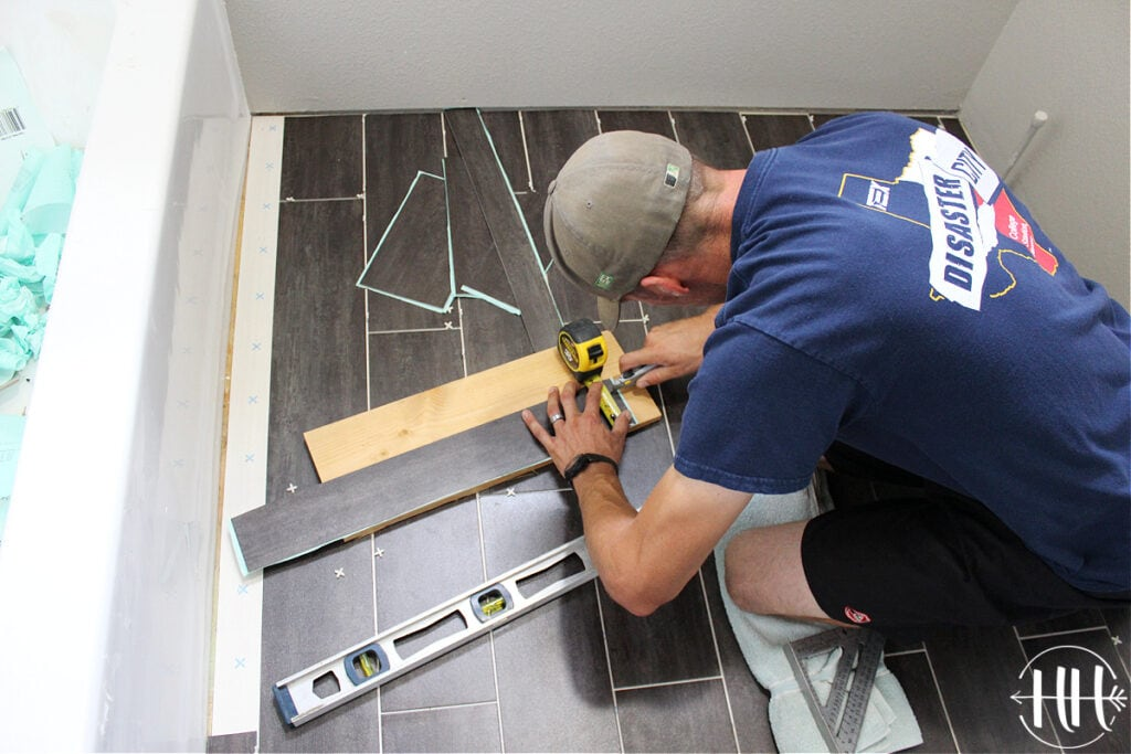 Cutting luxury vinyl tile planks with a knife on a scrap piece of wood.