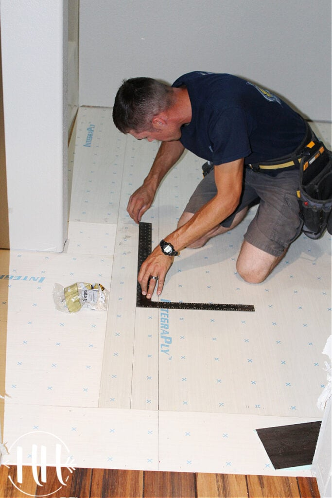 A contractor drawing a straight line with pencil on a subfloor.