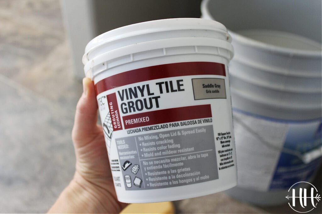 A container of Saddle Grey vinyl tile grout.