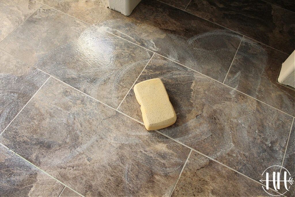 A large soft sponge mopping away the grout residue.
