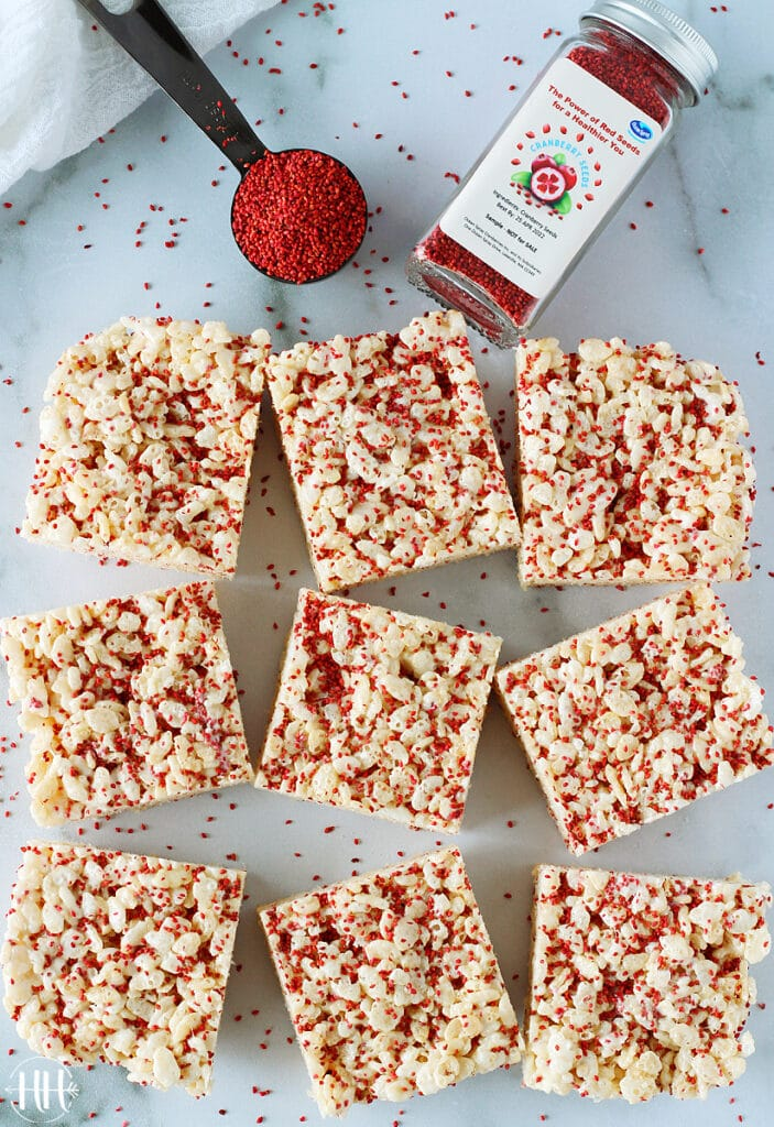 A bird's eye view of Cranberry Seeds Rice Krispie Treats and a glass jar of cranberry seeds.