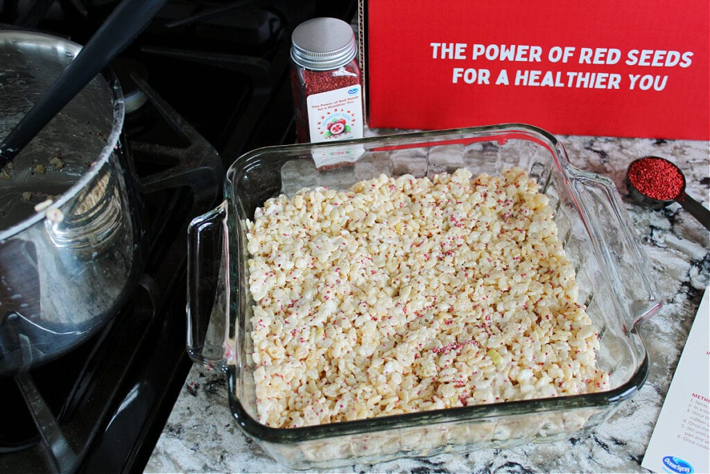 Cranberry Seed Rice Krispy Treats pressed into a glass 8x8 pan.